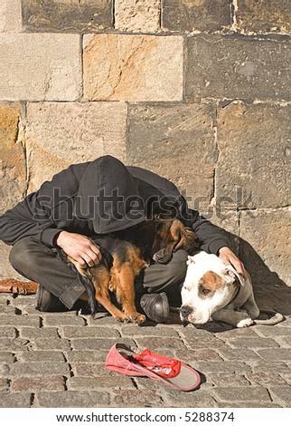 Hooded beggar with two Dogs on the Streets of Prague - stock photo