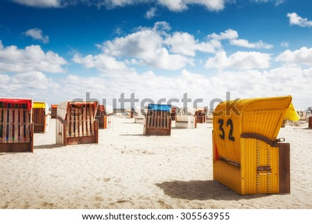 Hooded chairs on sand beach. Sunlight and blue cloudy sky. Vacation background. North sea coast, travel destination - stock photo
