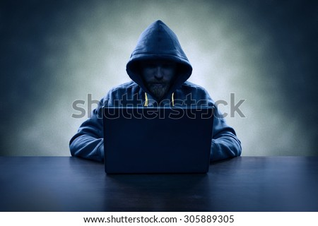 Hooded computer hacker stealing information with laptop - stock photo