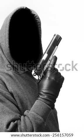 Hooded criminal carries a gun - stock photo