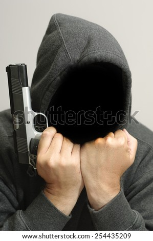 Hooded criminal with gun thinks about this next crime. - stock photo