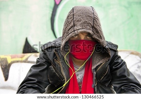 Hooded figure, wearing a scarf in front of his nose and mouth to disguise himself, looking menacing into the camera - stock photo