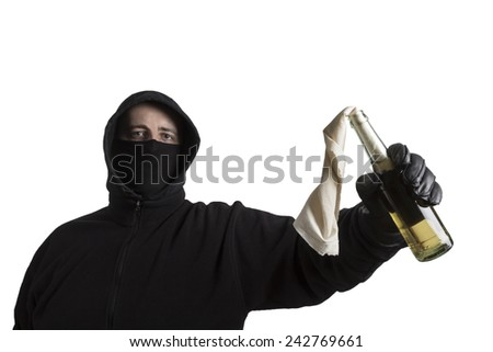 Hooded man in black dress holding a molotov cocktail isolated on white background - stock photo