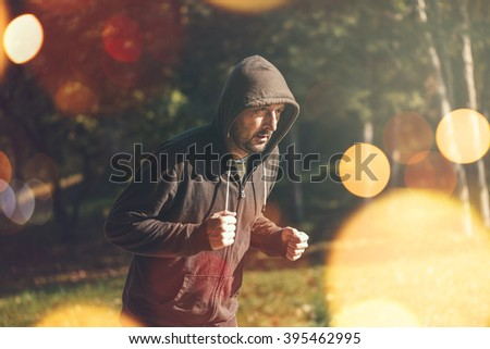 Hooded man jogging in the park in early autumn morning, healthy lifestyle concept, retro toned image with selective focus and bokeh light - stock photo
