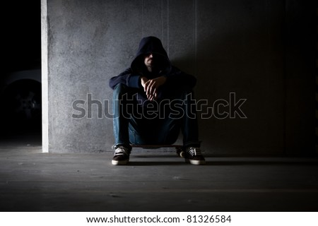 Hooded man sitting against wall.