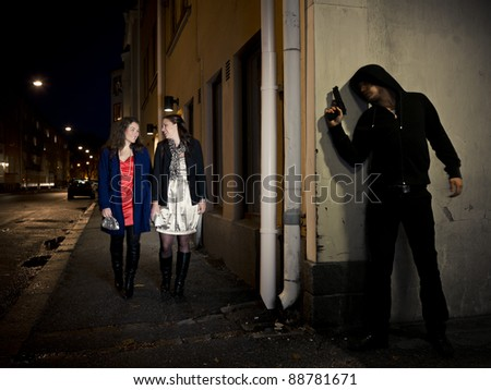 Hooded man stalking two women behind a corner holding a gun
