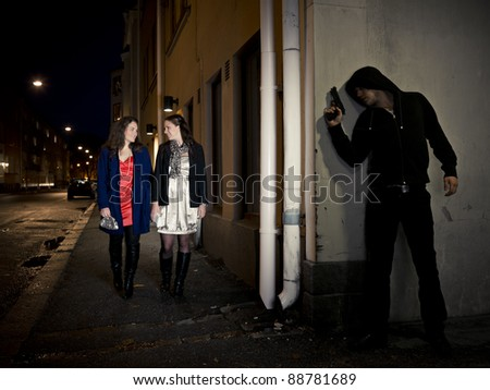 Hooded man stalking two women behind a corner holding a gun - stock photo