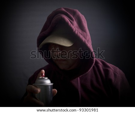 Hooded man with a spray can painting graffiti - stock photo