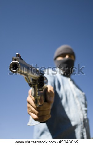 Hooded man with 44 magnum revolver threatening, wide angle view focus on handgun