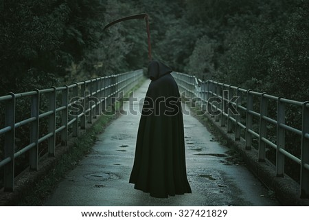 Hooded man with scythe waiting on a country bridge . Halloween and horror - stock photo