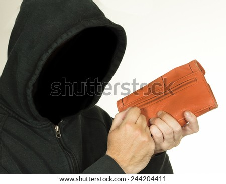 Hooded thug steals a wallet full of personal information and money - stock photo