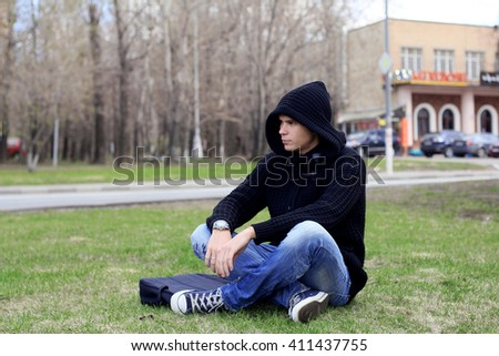 Hooded unisex student studying on computer while sitting cross-legged in jeans and sneakers in park on grass