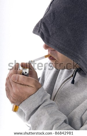 hooded young man lighting a cigarette on a white background