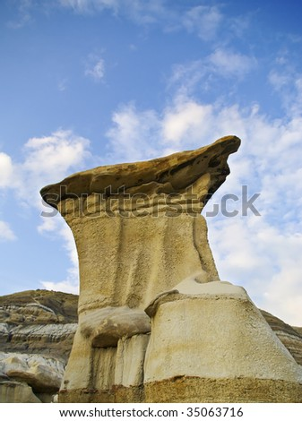 Hoodoo against blue sky and clouds - stock photo