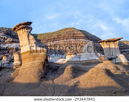 Hoodoos bathed in the warm light of a summer sunset at Drumheller Alberta Canada. - stock photo