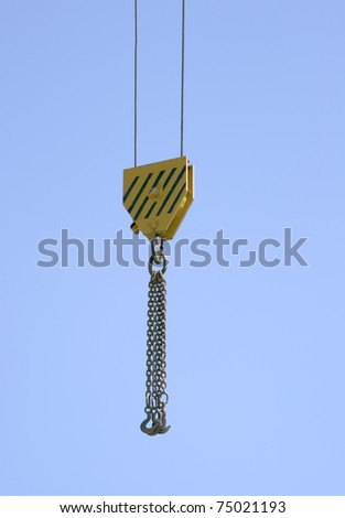 Hook of a lifting crane against clear blue sky - stock photo