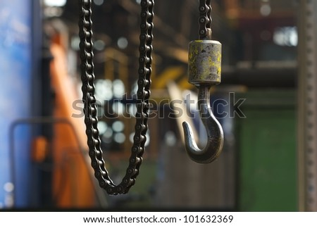 Hook on the chain in the industrial hall complex of heavy industry - stock photo