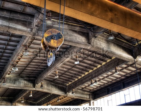 Hook on the crane in an old factory hall. - stock photo