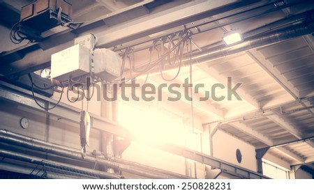Hook on the crane in an old factory hall, in sunny day. - stock photo
