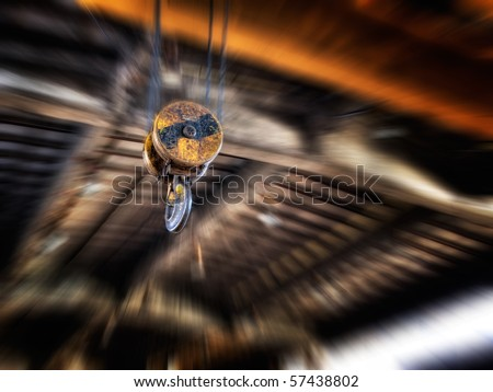 Hook on the crane in some old factory hall on a blurred background... - stock photo