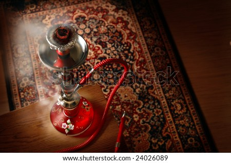 Hookah in smoke over a asian carpet
