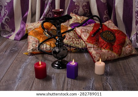 hookah on a background of oriental cushions and candles