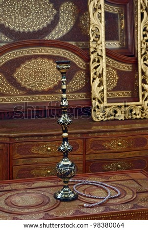 Hookah on a engaved table in a beautiful wooden room - stock photo