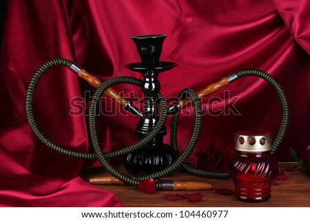 hookah on a wooden table on a background of red curtain close-up