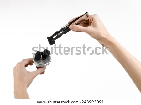 Hookah topic: Bartender holding a forceps with coal for hookah and puts them into a clay bowl isolated on white background - stock photo