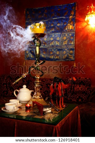 hookah with white smoke and tea cups on a table - stock photo