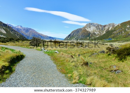 Hooker Valley on a track leading to Aoraki, Mount Cook, highest peak of Southern Alps, an icon of New Zealand partially covered in clouds - stock photo