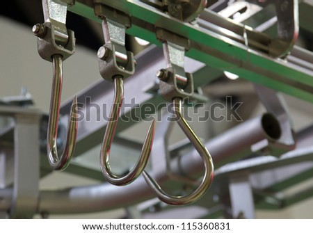 Hooks for meat in finishing shop of meat-packing plant - stock photo