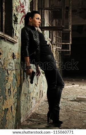 hooligan lady standing against the wall - stock photo