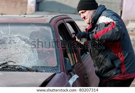 Hooligan smashing windshield - stock photo