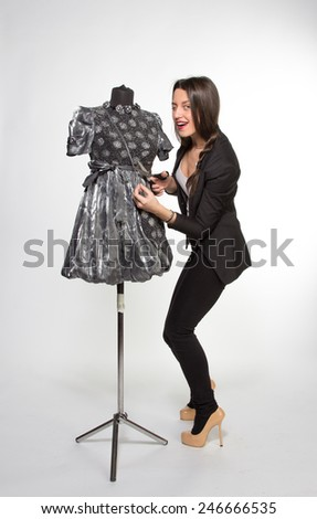 Hooligan Woman cutting something from dressed mannequin - stock photo