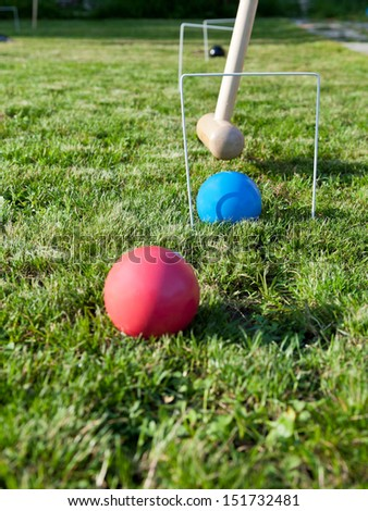 hoop and balls in game of croquet on green lawn in summer day - stock photo