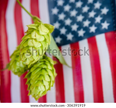 Hop flowers with the American flag in the background.