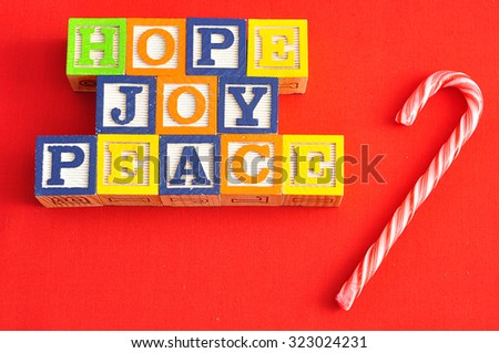 Hope, Joy and Peace spelled with  Alphabet blocks with a candy cane on a red background