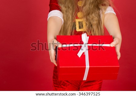 Hope you enjoy it. Cropped closeup of a little girl holding out a Christmas present box in her hands  - stock photo