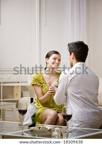 Hopeful man romantically proposing to surprised girlfriend and offering engagement ring - stock photo