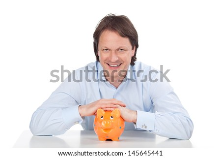 Hopeful man smiling with his piggy bank - stock photo