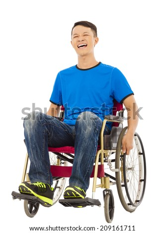 hopeful young man sitting on a wheelchair in studio - stock photo