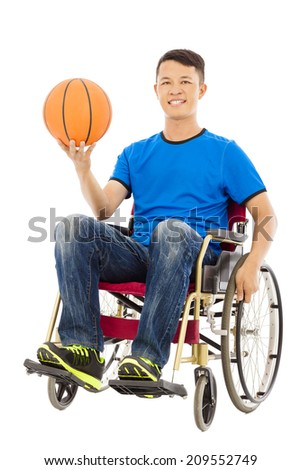 hopeful young man sitting on a wheelchair with a basketball - stock photo