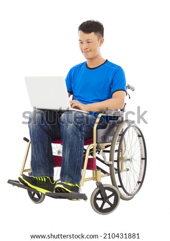 hopeful young man sitting on a wheelchair with a laptop - stock photo