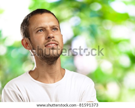 hopeful young man thinking about his future against a park background - stock photo