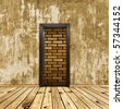 hopeless conceptual interior with door to brick wall - stock photo