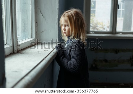 Hopeless life. Close up of depressed poor little girl standing near window and looking aside while feeling miserable - stock photo