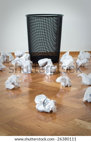 Hopelessly unsuccessful attempts, wastepaper bin with lots of paper balls on the floor none inside - stock photo