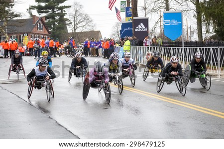 HOPKINTON, USA - APRIL 20: Athletes with disabilities competing in the Boston Marathon 2015 a few minutes after the start of the race in Hopkinton, MA, USA on April 20, 2015. - stock photo