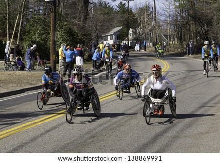 HOPKINTON, USA - APRIL 21: Athletes with disabilities heading fast and steadily from Hopkinton to Boston in MA, USA a few minutes after the start of the Boston Marathon 2014 on April 21, 2014. - stock photo